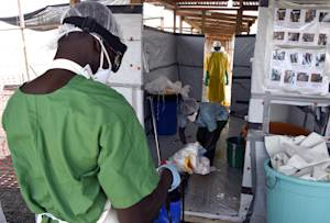 Health workers prepare to enter a decontamination room …