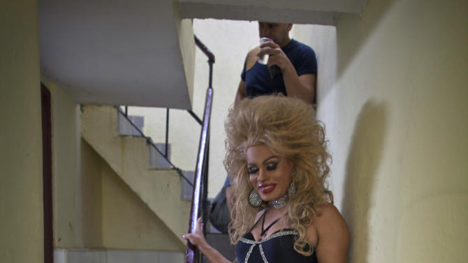"In this May 11, 2013 photo, Abrahan Bueno, 39, a gay transvestite artist known as ""Imperio,"" descends a flight of stairs as he makes his way to the stage at the Karl Marx theater in Havana, Cuba. A week of drag shows, colorful marches and social and cultural events in Havana culminates Friday with celebrations of the International Day Against Homophobia. Gays were persecuted for decades after the 1959 Cuban Revolution, sometimes sent to grueling rural work camps along with others considered socially suspect by the Communist government. But there has been a gradual shift away from macho attitudes, and Fidel Castro himself has publicly regretted the mistreatment of people seen as different. (AP Photo/Ramon Espinosa)"
