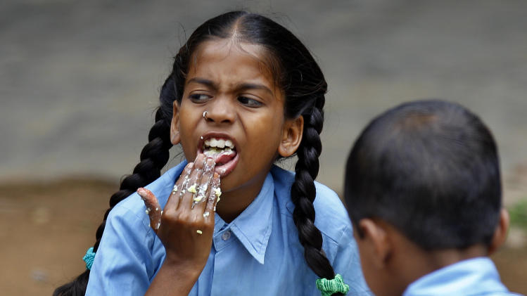 An Indian schoolgirl eats a free mid-day meal at a government run school on World Food Day in Bangalore, India, Tuesday, Oct. 16, 2012. Blaming flawed methodology and poor data, the United Nations says its 2009 headline-grabbing announcement that 1 billion people in the world were hungry was off-target and that the number is actually more like 870 million. (AP Photo/Aijaz Rahi)