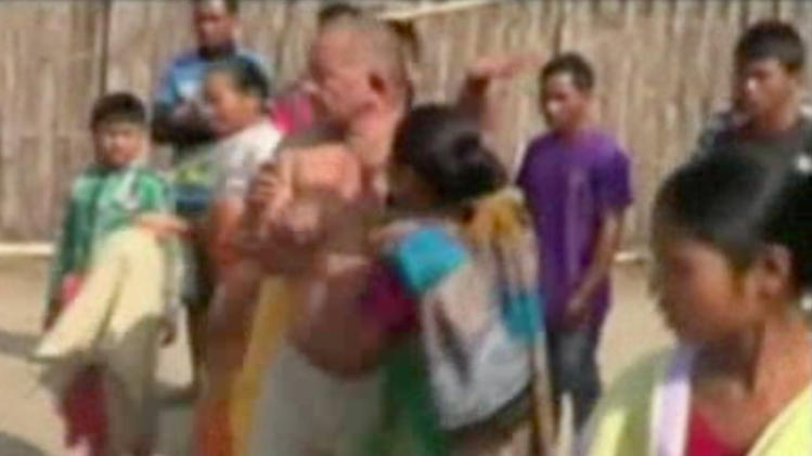 In this image taken from video obtained from Network 1 News and Information Syndicate (NNIS), which has been authenticated based on its contents and other AP reporting, Bikram Singh Brahma, center, a leader of India's ruling Congress party, is slapped by a woman in the village of Santipur, India, on Thursday, Jan. 3, 2013. Police said Brahma was visiting the village of Santipur on the Bhutan border when he entered a woman's house and raped her at 2 a.m. In a sign that attitudes might be changing since the rape of a 23-year-old woman in New Delhi, who died of severe internal injuries over the weekend, police have arrested Brahma. (AP Photo/NNIS)