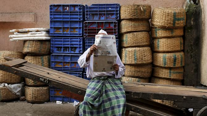 A man reads a newspaper while sitting on a handcart outside a wholesale fish market in Mumbai