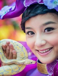 A model poses with a snake during an event to promote responsible snake breeding and pet ownership, in Kong Kong, on January 10, 2013. The Chinese new year, often referred to as the 'Lunar New Year', will mark the year of the snake on February 10