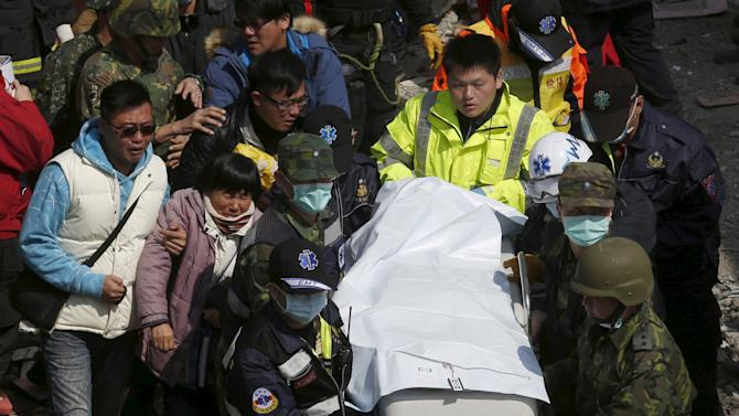 Relatives cry as they walk next to a body which was found at the site where a 17-storey apartment building collapsed after an earthquake hit Tainan