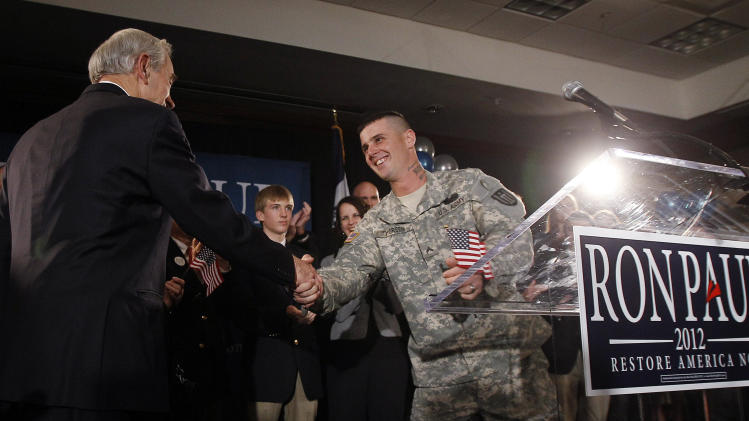 FILE - In this Jan. 3, 2012, file photo, Republican presidential candidate Rep. Ron Paul, R-Texas, left, shakes hands with Cpl. Jesse Thorsen during his caucus night rally, in Ankeny, Iowa. Army records obtained Tuesday, May 1, 2012,  by The Associated Press under the Freedom of Information Act show Paul's presidential campaign didn't cooperate with the Army's disciplinary investigation of Thorsen, who was reprimanded in March for participating in a partisan political event in uniform. (AP Photo/Eric Gay, File)