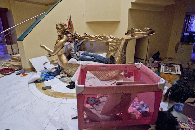 """Rebel fighter poses for a photo as he sit on a two seater couch that framed by golden mermaid with the face of Aisha Gadhafi the daughter of Libyan dictator Moammar Gadhafi in her house in Tripoli, Libya, Wednesday, Aug. 24, 2011. A defiant Moammar Gadhafi vowed Wednesday to fight on """"until victory or martyrdom,"""" as rebel fighters tried to end scattered attacks by regime loyalists in the nervous capital. (AP Photo/Sergey Ponomarev)"""