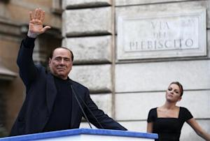 Former Italian Prime Minister Silvio Berlusconi waves to supporters as his girlfriend Francesca Pascale looks on during a rally to protest his tax fraud conviction, outside his palace in central Rome