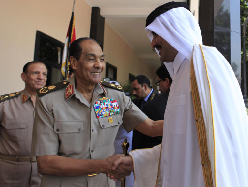 Field Marshal Hussein Tantawi, the head of the Egyptian Armed Forces Supreme Council, center, shakes hands with Crown Prince of Qatar Sheikh Tamem Bin Hamad ahead of their meeting at his office in Cairo, Egypt Thursday June 30, 2011. Others are unidentified. (AP Photo/Amel Pain, Pool)