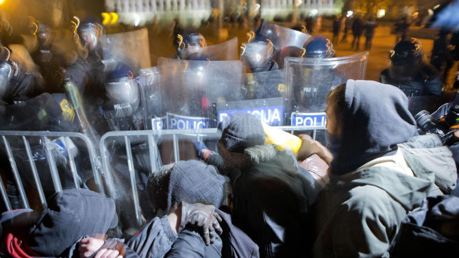 """Protesters clash with riot police in front of the parliament building, in Ljubljana, Slovenia, Friday, Jan. 11, 2013. About 10,000 protesters joined the chief of Slovenia's anti-corruption watchdog on Friday in urging the country's prime minister and opposition leader to resign after an official report accused them of graft.  """"Thieves! Thieves!"""" many of the demonstrators chanted as they accused Prime Minister Janez Jansa and opposition leader Zoran Jankovic of corruption. The protesters burned photos of both men in front of Parliament. (AP Photo/Darko Bandic)"""