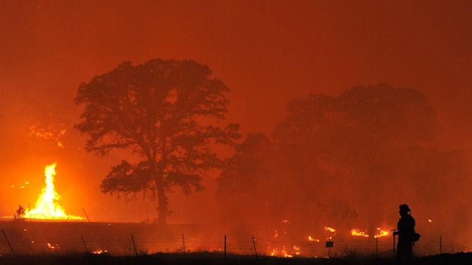 A firefighter watches a backfire as the Rocky Fire burns near Clearlake, Calif., on Monday, Aug. 3, 2015. The fire has charred more than 60,000 acres and destroyed at least 24 residences. (AP Photo/Josh Edelson)