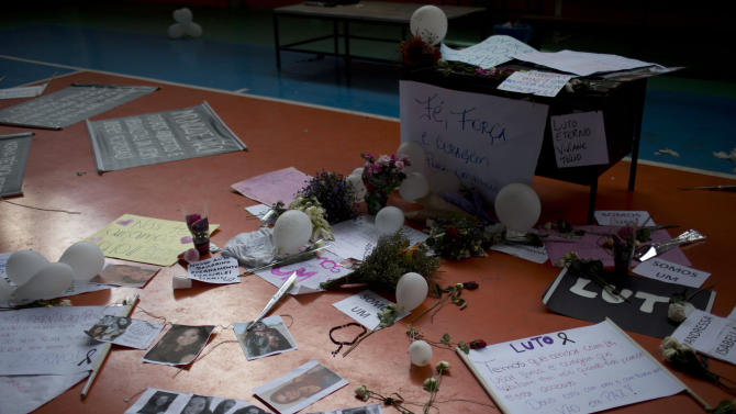 A makeshift memorial that include pictures of the victims of the Kiss nightclub fatal fire begins to form inside a gymnasium where a collective funeral was held a day earlier, in Santa Maria, Brazil, Tuesday, Jan. 29, 2013. A fast-moving fire roared through the crowded, windowless Kiss nightclub in this southern Brazilian city early Sunday, killing more than 230 people.  The first funeral services were held Monday for the victims. Most of the dead were college students 18 to 21 years old, but they also included some minors. Almost all died from smoke inhalation rather than burns. (AP Photo/Felipe Dana)