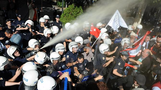 Riot police spray pepper gas toward people, who were holding national flags and poster of Turkey's founder Kemal Ataturk, as they march to the mausoleum of Ataturk to celebrate the Republic Day in Ankara, Turkey, Monday, Oct. 29 2012. Police on Monday used tear gas and water cannons to try to break up a demonstration by tens of thousands of pro-secular protesters, but the march to mark the founding of the Turkish republic went on in defiance of a government ban.(AP Photo/Burhan Ozbilici)