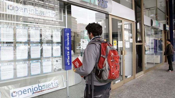 A man checks job offers outside a recruitment agency in downtown Milan