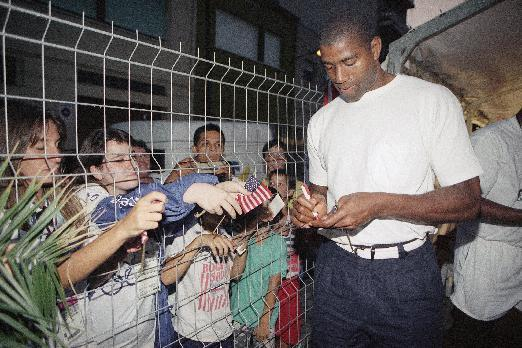 In this July 28, 1992, file photo, U.S. Olympic basketball player Magic Johnson signs autographs for local children in Barcelona, Spain