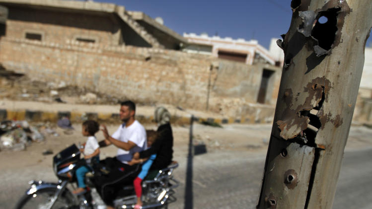 In this Sunday Aug. 5, 2012 photo, a Syrian family on a motorcycle passes by a bullet riddled street lamp post in the town of Atareb on the outskirts of Aleppo, Syria. (AP Photo)