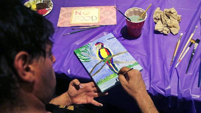Chris Haubrich, a homeless artist, paints at the Emmanuel Episcopal Church in Boston, Wednesday, Sept. 30, 2015. At the Boston church, many homeless participate in the Common Art program, which is designed not only to give them a place to stay warm, but an opportunity to express themselves, learn some life skills and gain self-esteem. (AP Photo/Charles Krupa)