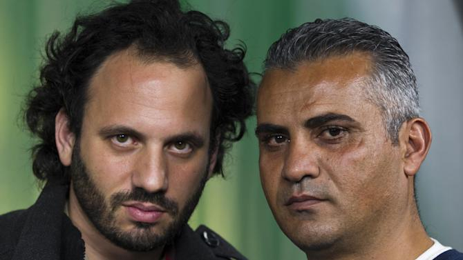 "In this Tuesday, Feb. 5, 2013 photo, documentary film Co-directors, Israeli, Guy Davidi, left, and Palestinian, Emad Burnat, pose for a photo after an interview in Los Angeles. Their 2011 documentary film, ""5 Broken Cameras,"" is nominated for an Oscar in the best Documentary Feature category.  (AP Photo/Damian Dovarganes)"