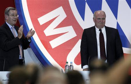 Bayern Munich's President Uli Hoeness receives a standing ovation from CFO Karl Hopfner and supporters during an annual meeting of the German Bundesliga first division soccer club in Munich