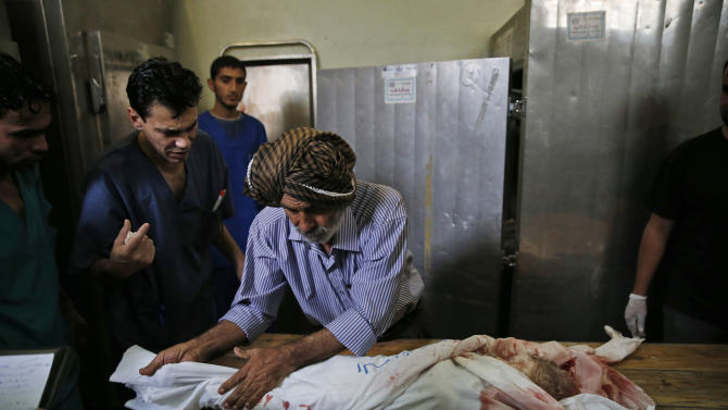 Palestinian Ahmed Jadallah, centre, 75, prepares a child's body for burial at the morgue of Kamal Adwan hospital in Beit Lahiya, northern Gaza Strip, Thursday, July 24, 2014. Over the past three decades, the 75-year-old Jadallah has dressed hundreds of 'martyrs' _ those killed in conflict with Israel. He said his volunteer work fulfills an Islamic commandment and that he hopes it will earn him a place in paradise. (AP Photo/Lefteris Pitarakis)