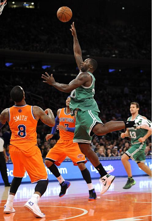 Boston Celtics' Brandon Bass (30) shoots over New York Knicks' J.R. Smith (8) and Carmelo Anthony (7) in the first half an NBA basketball game on Sunday, Dec. 8, 2013, in New York. The Celtics
