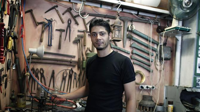 "WITH STORY GREECE VOICES BY NIKOS PAPHITIS : Metalworking craftsman Apostolos Liamiras, 26, poses in his traditional coppersmith's shop in the Psyrri district of central Athens, on Thursday, Aug. 23, 2012. As Greek Prime Minister Antonis Samaras sets off around Europe to plead for more time to achieve the country's tough reform targets, austerity-weary Greeks are bracing for new pain but mostly expect to stay in the 17-nation eurozone, come what may. Liamiras said it would have been better if Greece had never joined the currency union. ""Leaving it wouldn't do any good, it would make things worse and create bigger problems,"" he said.(AP Photo/Petros Giannakouris)"
