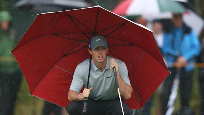Rory McIlroy of Northern Ireland kneels under an umbrella as he waits to play on the 4th green during the third day of the British Open Golf championship at the Royal Liverpool golf club, Hoylake, England, Saturday July 19, 2014. (AP Photo/Jon Super)