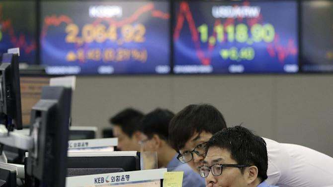 Currency traders watch monitors at the foreign exchange dealing room of the Korea Exchange Bank headquarters in Seoul, South Korea, Tuesday, June 30, 2015. Asian stock markets bounced back Tuesday, recouping some of the previous day's sharp losses, but investors remained worried the crisis in Greece could spread to other financially weak countries. (AP Photo/Ahn Young-joon)