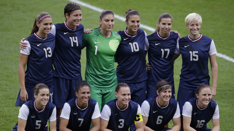 The United States women's soccer team poses for photographs before their gold medal match against Japan at the 2012 Summer Olympics, Thursday, Aug. 9, 2012, in London. (AP Photo/Andrew Medichini)
