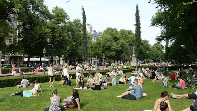 In this June 26, 2013 photo, people cool off on a hot summer day in Esplanade Park in Helsinki, Finland. In summer, glorious sun-filled days draw picnickers to every available last patch of grass. (AP Photo/Lehtikuva, Martti Kainulainen) FINLAND OUT