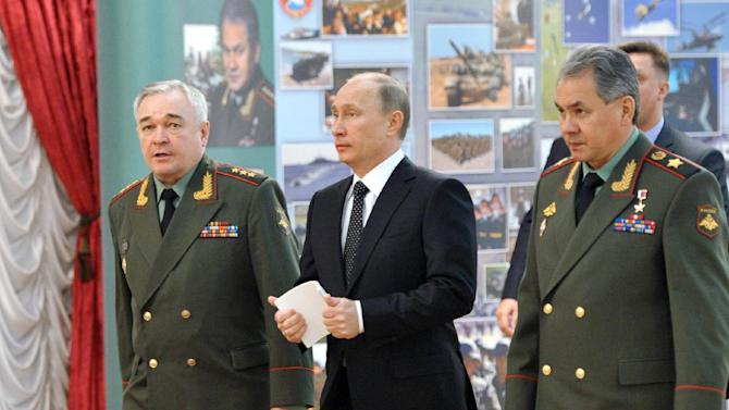 """Russian President Vladimir Putin, center, and Defense Minister Sergei Shoigu, right, walk to meet senior military officials in Moscow on Wednesday, Feb. 27, 2013. Russian President Vladimir Putin has called on the country's top brass to deliver a drastic upgrade of the armed forces in the next three years to fend off attempts from abroad to """"tip the strategic balance"""" in the world. (AP Photo/RIA Novosti, Alexei Nikolsky, Presidential Press Service)"""