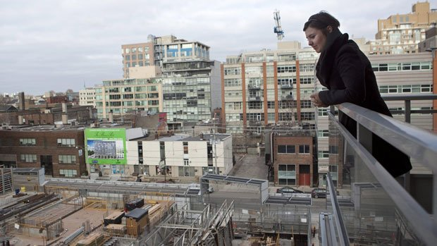 A condo owner looks onto a neighbouring condo under construction in Toronto. RBC says housing affordability eroded during the past three months.