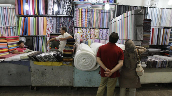 In this picture taken on Saturday, July 14, 2012, two potential Iranian customers look at fabric bolts in Tehran's old main bazaar, Iran, as two merchants sit at left. While Iran's mainstay oil exports remains the centerpiece of Western sanctions _ intended to wring concessions on Iran's nuclear program and ease Israeli threats of a military strike _ the Islamic Republic hangs on as OPEC's third-largest exporter as it feeds the hungry energy markets in China, India and across Asia. But less noted _ but potentially more unsettling to Iran's leaders in the coming months _ is the increasing pinch on the workaday economy: The commerce, transactions and trading that provide the paychecks and economic lifelines for millions of people.(AP Photo/Vahid Salemi)