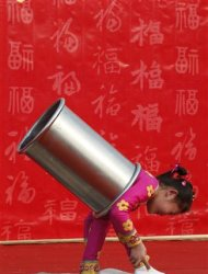 A girl performs an acrobatic show during the temple fair in Ditan Park, also known as the Temple of Earth, in Beijing February 9, 2013. The Lunar New Year, or Spring Festival, begins on February 10 and marks the start of the Year of the Snake, according to the Chinese zodiac. REUTERS/Kim Kyung-Hoon