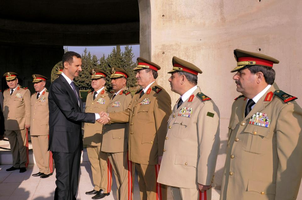 In this photo released by the Syrian official news agency SANA, Syrian President Bashar Assad greets military officers in a ceremony marking the anniversary of the 1973 Arab-Israeli war in Damascus, Syria, Saturday, October 6, 2012. (AP Photo/SANA)
