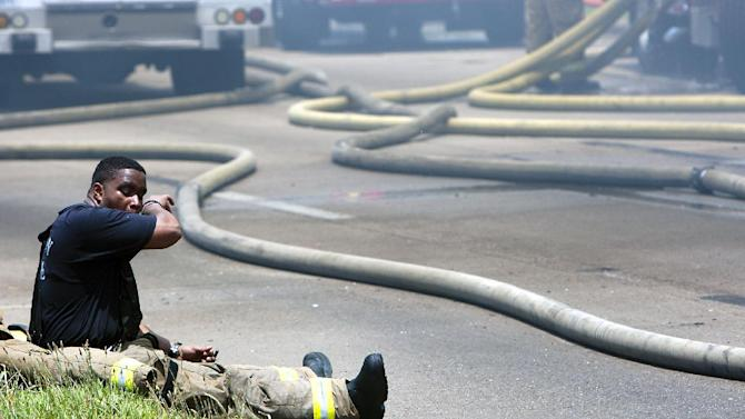 A firefighter sits on the ground during a blaze at the Southwest Inn on U.S. 59 in Houston on Friday, May 31, 2013. (AP Photo/Houston Chronicle, Cody Duty)