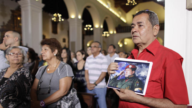 "People, one of them holding an image of Venezuela's President Hugo Chavez, gather to pray for him at a church in Caracas, Venezuela, Monday, Dec. 31, 2012. Venezuela's President Hugo Chavez is confronting ""new complications"" due to a respiratory infection nearly three weeks after undergoing cancer surgery, his Vice President Nicolas Maduro said Sunday evening in Cuba as he visited the ailing leader for the first time since his operation. (AP Photo/Ariana Cubillos)"