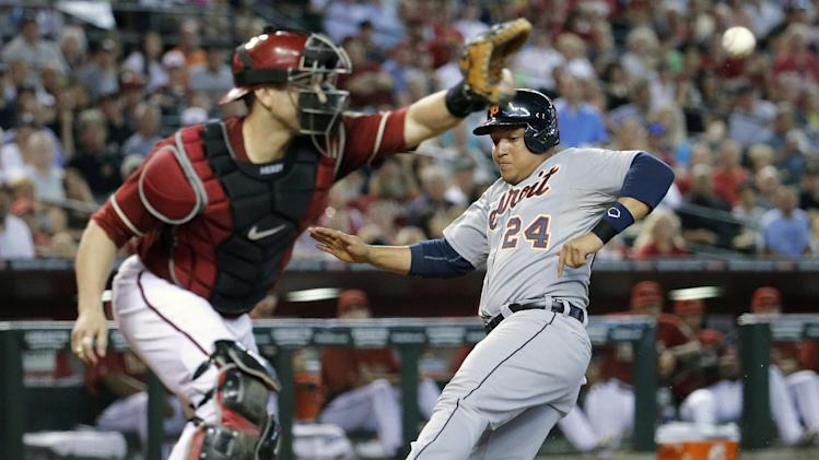 Detroit Tigers' Miguel Cabrera (24) scores on a sacrifice fly by teammate Alex Avila as Arizona Diamondbacks catcher Miguel Montero makes the catch during the fourth inning of a baseball game, Wednesday, July 23, 2014, in Phoenix. (AP Photo/Matt York)