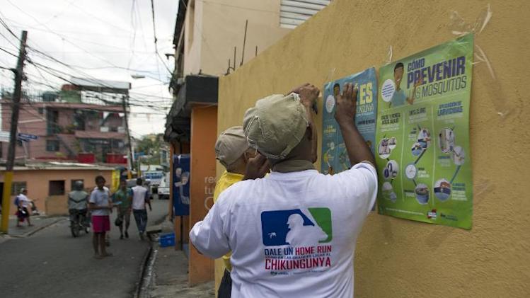 Employees of the Dominican Ministry of Public Health stick posters on a wall during an information campaign to prevent the spread of the mosquito which transmits the Chikungunya virus in Santo Domingo on May 30, 2014