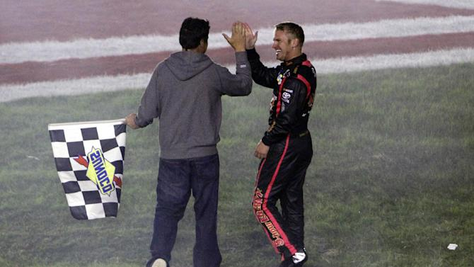 In this pool photo provided by HHP Images, Clint Bowyer, right, celebrates with team owner Michael Waltrip, left, after winning the NASCAR Bank of America 500 Sprint Cup series auto race in Concord, N.C., Saturday, Oct. 13, 2012. (AP Photo/Brian Lawdermilk, Pool)