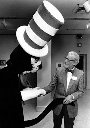 Theodor Seuss Geisel, better-known as Dr. Seuss, shakes hands with Cat in the Hat at the New Orleans Museum of Fine Arts in Louisiana on Feb. 13, 1988. (AP Photo/Burt Steel)