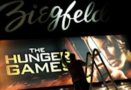 "A worker swaps out the billboard marking the opening of ""The Hunger Games"" on March 22 at the Ziegfeld Theatre in New York. ""The Hunger Games"" took nearly $20 million in midnight screenings alone Friday in the United States, the seventh best ever, industry tracker Exhibitor Relations said"
