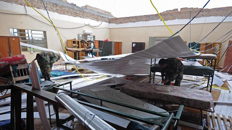 ** CORRECTS DATE ** Officers inspect a Paraguayan Army Logistic Command dormitory where four military cadets were killed when their roof caved in during an overnight storm, in Mariano Roque Alonso, Paraguay, Wednesday, Sept. 19, 2012. A powerful storm killed five people and injured 81 in Paraguay as a storm blew across the southern cone of South America, ripping the roofs off of ramshackle homes and leaving thousands of people without shelter. (AP Photo)
