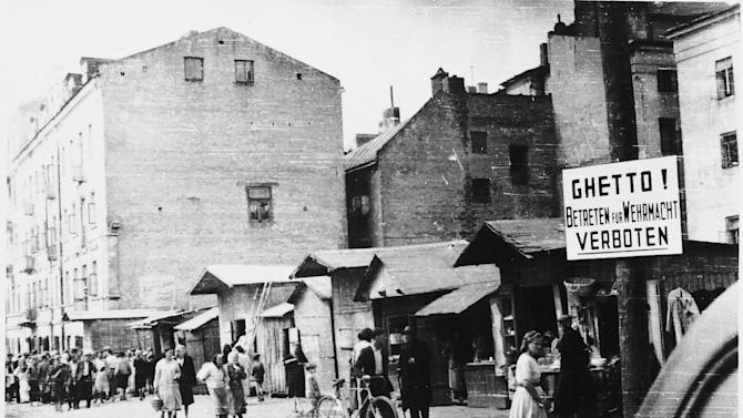 "In this ca. 1941-1942 photo provided by the United States Holocaust Memorial Museum, people walk on a commercial street in the Lublin ghetto near a sign forbidding entry, in Warsaw, Poland. Despite all the Holocaust writings, more news is emerging about 1,000 Nazi-run ghettos that left millions of Jews dead. ""Encyclopedia of Camps and Ghettos, 1933-1945, Volume II""  is a global effort that documents every site of organized Nazi atrocities. (AP Photo/United States Holocaust Memorial Museum) MANDATORY CREDIT: UNITED STATES HOLOCAUST MEMEORIAL MUSEUM. ONE TIME USE ONLY, NO ARCHIVING"