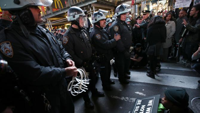 New York City Police NYPD officers prepare to detain people blocking traffic as they protest against the verdict announced in the shooting death of Michael Brown, in Times Square, New York