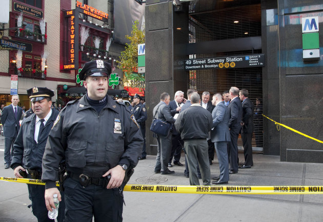 Uniformed and plainclothes police officers stand outside a New York subway station after a man was killed after falling into the path of a train, Monday, Dec. 3, 2012. Transit officials say police are investigating whether he could have been pushed onto the tracks. (AP Photo/Mark Lennihan)