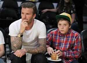 Soccer star David Beckham and his son Brooklyn watch the Los Angeles Lakers play the Miami Heat in their NBA basketball game in Los Angeles