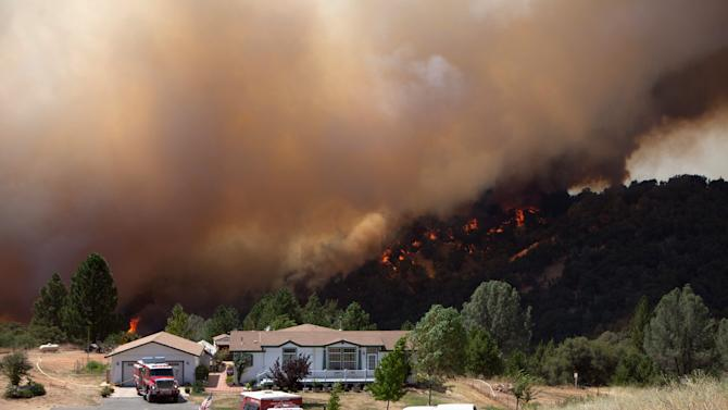 "Firefighters protect an evacuated home while the ""Sand Fire"" burns behind, near Plymouth, California"