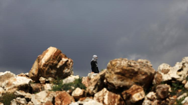A stone-throwing Palestinian protester stands during clashes with Israeli troops at a weekly protest against Jewish settlements, near Ramallah