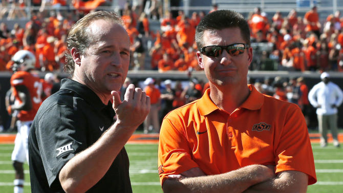 West Virginia head coach Dana Holgorson, left,talks with Oklahoma State head coach Mike Gundy, right, before the start of an NCAA college football game in Stillwater, Okla., Saturday, Oct. 25, 2014. (AP Photo/Sue Ogrocki)