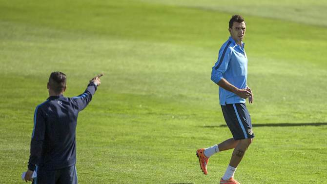 Atletico's Mario Mandzukic runs as Diego Simeone, left, supervise a training session ahead of Wednesday's Champions League soccer match between Atletico Madrid and Juventus, in Madrid, Spain, Tuesday, Sept. 30, 2014