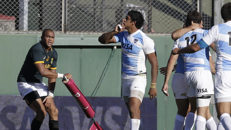 Argentina's Manuel Montero, center, reacts after scoring a try against South Africa as South Africa's Cornal Hendricks, left, looks on during their Rugby Championship match in Salta, Argentina, Saturday, Aug. 23, 2014. (AP Photo/Victor R. Caivano)